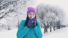 Brunette girl drinks hot tea in winter in park closing her eyes. After training Stock Photo