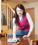 Brunette girl dusting wooden table Stock Photo