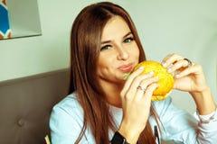 Brunette girl eats hamburger stock photo