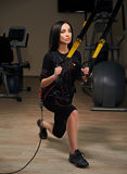 Brunette girl in EMS suit do squat exercise for back with trx suspension. Brunette girl in Electrical Muscular Stimulation suit doing squat exercise for back and royalty free stock image