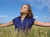 Brunette girl enjoing the sun. In a field Stock Images