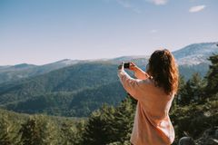 A girl takes a picture of the mountains and forests around her on a sunny day stock image