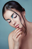 Brunette girl with fashion wet hairstyle and beautiful makeup on blue background. Beautiful model with perfect makeup. Woman with beautiful hands hairstyle and Stock Image