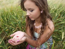 Brunette girl in a field with ladybug Royalty Free Stock Photos