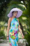 Brunette girl in flower dress and pink hat Stock Photo