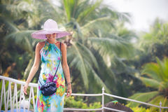 Brunette girl in flower dress and pink hat Royalty Free Stock Image