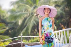 Brunette girl in flower dress and pink hat Stock Photography