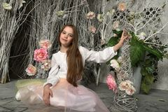 Brunette girl among flowers. In fairytale decorations Royalty Free Stock Image