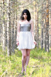 Brunette girl in forest in white dress Stock Photo