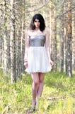 Brunette girl in forest in white dress. Daylight Stock Photo