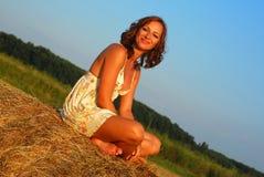 Brunette girl on fresh straw Stock Image