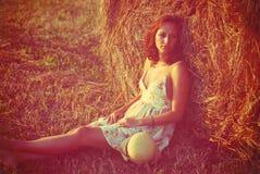 Brunette girl on fresh straw Stock Photography