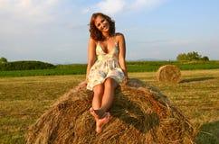 Brunette girl on fresh straw Royalty Free Stock Image