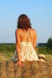 Brunette girl on fresh straw royalty free stock photos