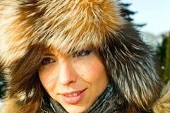 Brunette girl in fur-cap royalty free stock photo