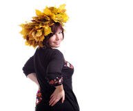 Brunette girl with garland of yellow leaves. European brunette girl in black dress with garland of yellow maple leaves on head Royalty Free Stock Photos
