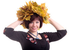 Brunette girl with garland of yellow leaves. European brunette short-haired girl in black dress with garland of yellow maple leaves on head Royalty Free Stock Images