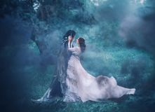Brunette girl ghost and spirit of nightly mysterious cold blue forest, lady in white vintage lace dress with long flying