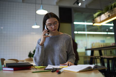 The brunette girl in glasses performs daily work consultation with skilled economists advising solution of big amount of outlay Royalty Free Stock Image