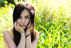 Brunette girl on green grass at summer park. Portrait of young beautiful woman Royalty Free Stock Image