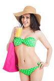 Brunette girl in green swimsuit and hat, holding  glass of juice Royalty Free Stock Image