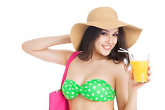 Brunette girl in green swimsuit and hat, holding glass of orange Stock Photos