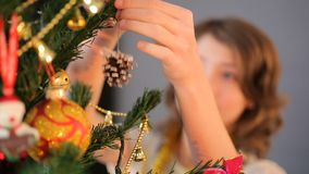 Brunette girl hanging Christmas toy on fir tree in the evening before holiday stock footage