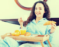 Brunette girl having breakfast in bed and smiling Royalty Free Stock Images
