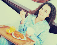 Brunette girl having breakfast in bed and smiling Royalty Free Stock Photo