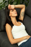 Brunette girl with headache resting on the sofa Royalty Free Stock Photography