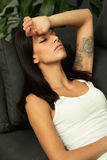 Brunette girl with headache resting on the sofa Stock Image