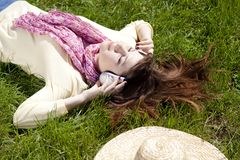 Brunette girl with headphone lies in the park Royalty Free Stock Photography