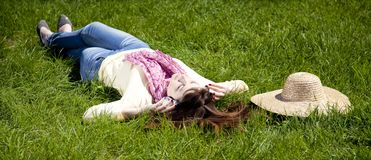Brunette girl with headphone lies in the park Stock Images
