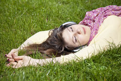 Brunette girl with headphone lies in the park Stock Photo