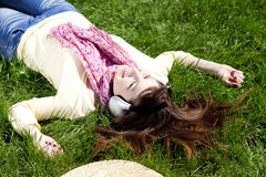 Brunette girl with headphone lies in the park. Royalty Free Stock Photos