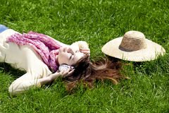Brunette girl with headphone lies in the park. Royalty Free Stock Images