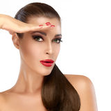 Brunette Girl with Healthy Long Hair. Trendy Hairstyle and Makeu. Beautiful fashion model with healthy long hair and hand on forehead like a visor. Woman Royalty Free Stock Photography