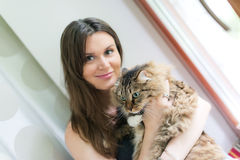 Brunette girl and her ginger cat Royalty Free Stock Images
