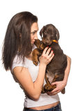 Brunette girl with her puppy isolated on white background Royalty Free Stock Photography