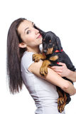 Brunette girl with her puppy isolated on white background Royalty Free Stock Images