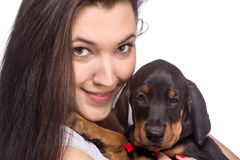 Brunette girl with her puppy isolated on white background Stock Photography