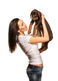 Brunette girl with her puppy isolated on white background Royalty Free Stock Photos