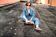 Brunette girl, hipster woman with skateboard, sunglasses and jeans outfit. Royalty Free Stock Photography