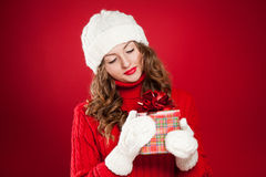 Brunette girl holding Christmas present wearing hat and mittens Stock Images