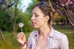 Brunette girl holding a dandelion royalty free stock image