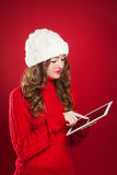 Brunette girl  holding ipad touchs screen searing internet. Beautiful brunette girl wearing red sweater and holding ipad touchs screen searing internet over red Royalty Free Stock Images