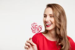 The brunette girl is holding a lollipop as a heart and laughing. For Valentine`s Day Stock Photo