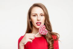 The brunette girl is holding a lollipop as a heart . For Valentine`s Day. On white background royalty free stock photo