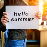 Brunette girl holding paper with Hello Summer phrase in rays of Stock Images