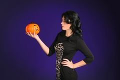 Brunette girl holding a pumpkin in hand Royalty Free Stock Images